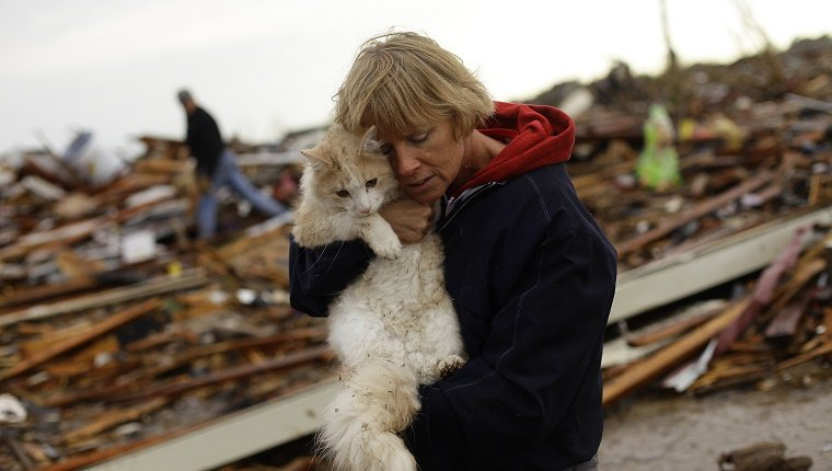 A woman holds her cat in front of a house that has been destroyed by a tornado.