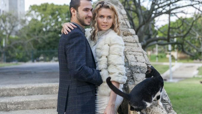 model couple stands in park with cat near by