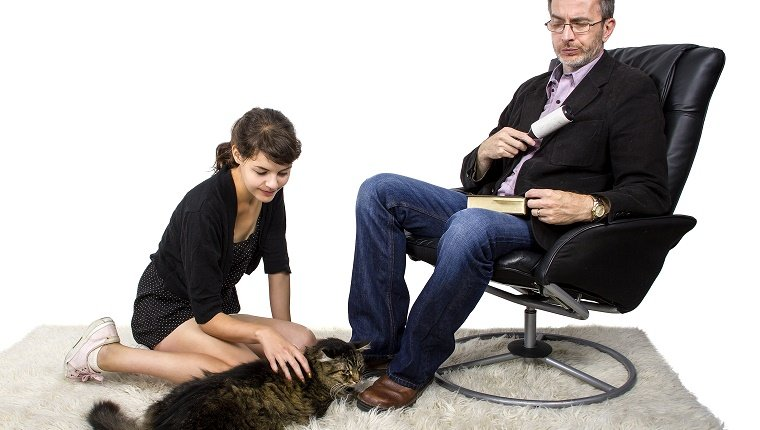 Father cleaning off daughters cat fur and dander off his jacket. The man is using a lint roller to clean his jacket. The daughter is playing with an adopted pet cat. The man looks like he dislikes the new pet because of the mess or he is allergic.
