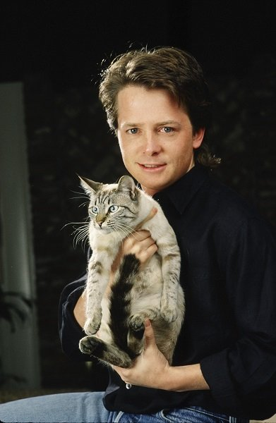 """BEVERLY HILLS, CA - 1988: Actor Michael J. Fox poses with his cat during a 1988 Beverly Hills, California, photo portrait session. Fox, a three-time Emmy Award winner for his work on TV's """"Family Ties,"""" also starred in the """"Back to the Future"""" film trilogy. (Photo by George Rose/Getty Images)"""