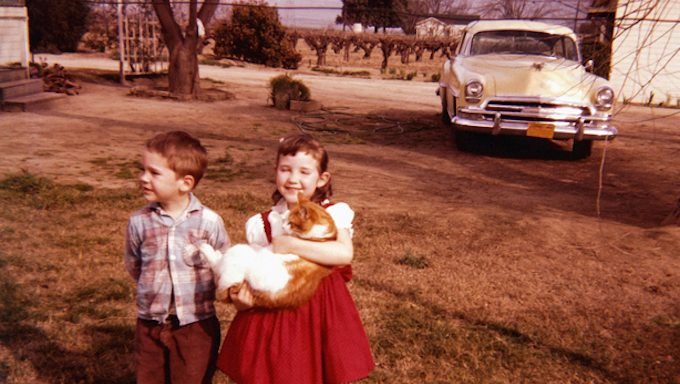 old photo of kids on lawn with cat