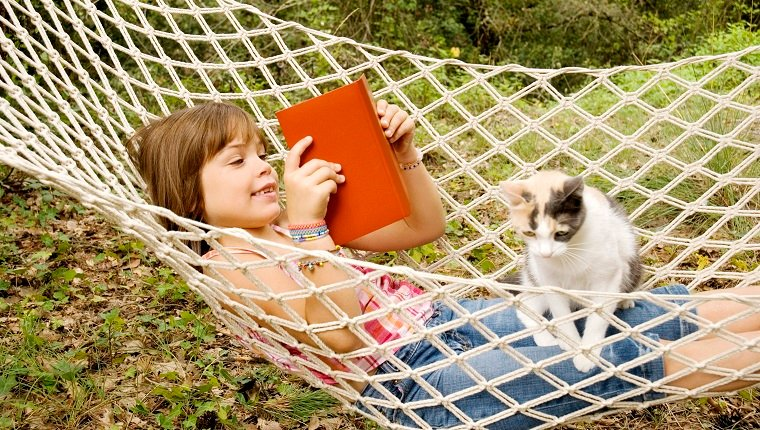 Seven years old reading about cat facts in a hammock with her cat on her lap.