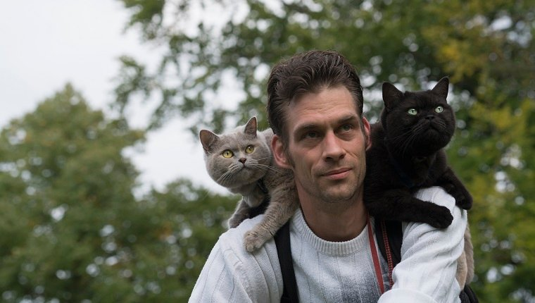 Male on a bike with 2 cats enjoying the ride on his shoulder.