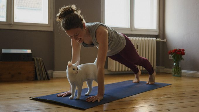 woman stretching with cat