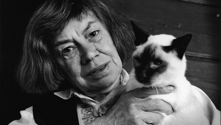 Portrait of American mystery and suspense author Patricia Highsmith (1921 - 1995), creator of the character Tom Ripley, as she holds a Siamese cat, 1991.