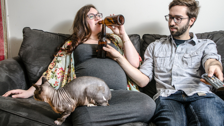 Pregnant woman drinking beer with her cat