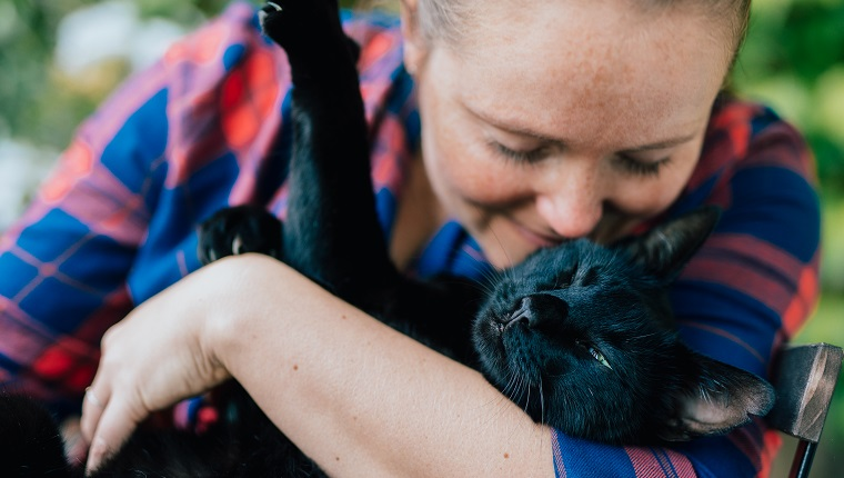 Portrait of blondhaired woman hugging her black cat outdoor.