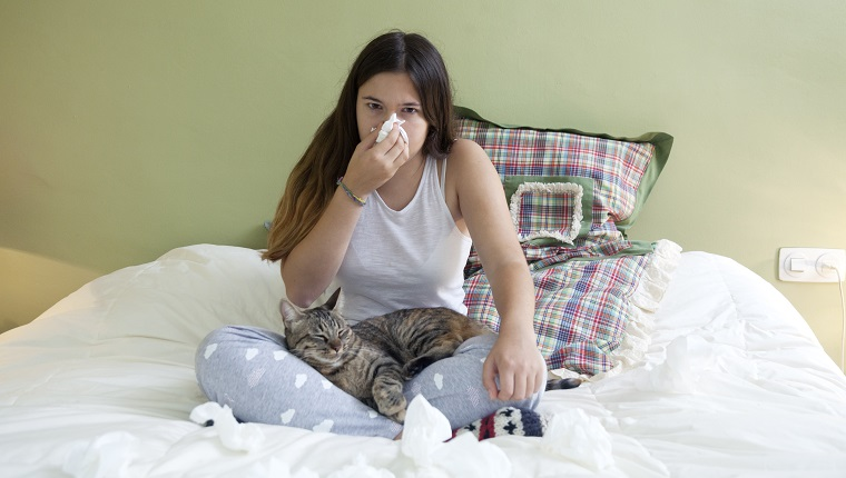 Girl sitting on the bed with cat allergy