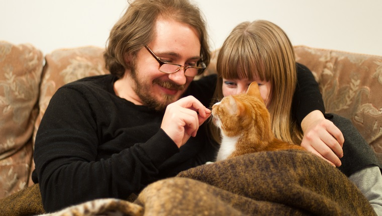 A young couple - a brunette man with glasses and a blonde woman, sit on a sofa cuddling and giving treats to their pet ginger cat.