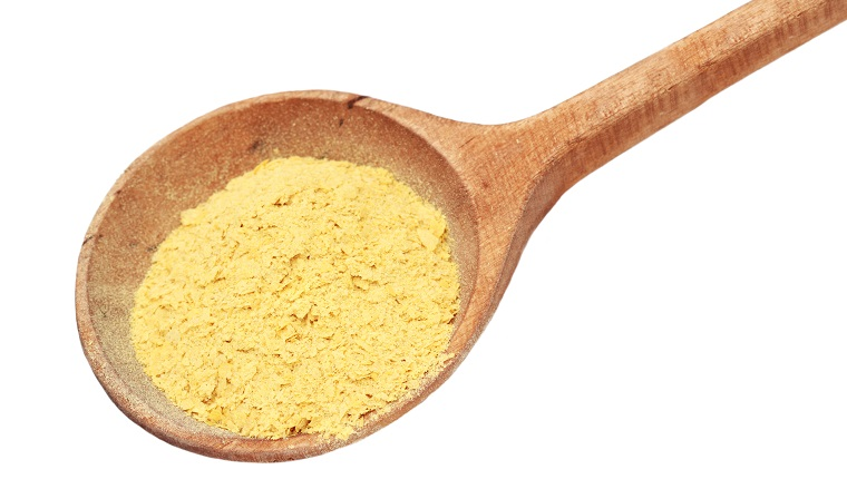 Nutritional yeast flakes in a wooden spoon isolated on white with clipping path.