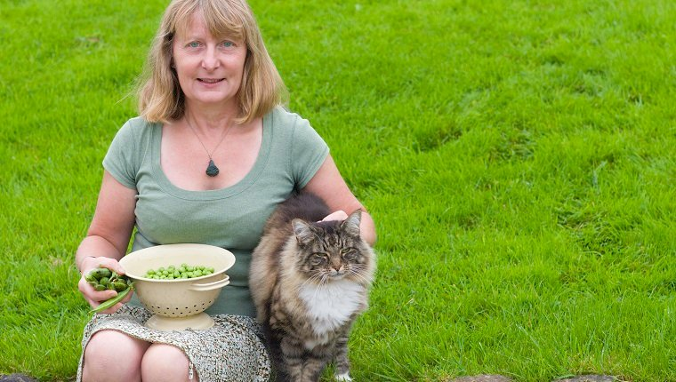 A contented gardener with her freshly grown peas and her contented cat.