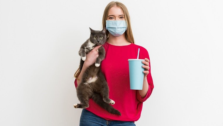 young woman in medical mask holding in arms cute cat and disposable cup with soda isolated on white