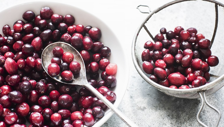 Fresh cranberries in a white bowl with spoon