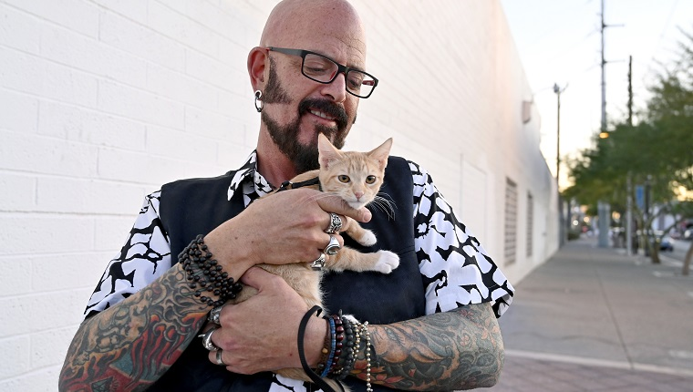 """LAS VEGAS, NEVADA - NOVEMBER 07: Television personality Jackson Galaxy from Animal Planet's """"My Cat From Hell"""" poses with Bonni, a four-month-old domestic shorthair orange tabby cat before an unveiling and rededication of an artwork titled, """"Snowball in Vegas,"""" during a ceremony in which the city of Las Vegas proclaimed Thursday """"Cat Appreciation Day"""" on November 7, 2019 in Las Vegas, Nevada."""